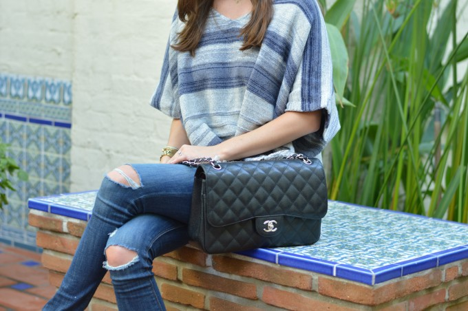 black chanel quilted handbag, striped poncho with fringe