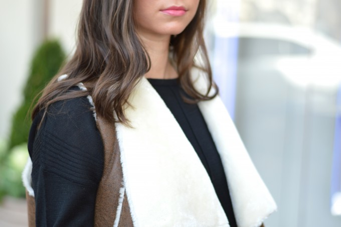 brown shearling vest, pink lipgloss, black crewneck sweater
