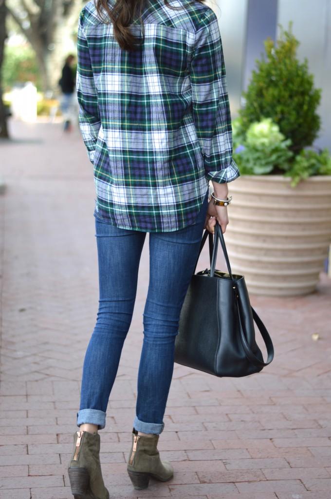 olive green booties, distressed denim, black statement handbag
