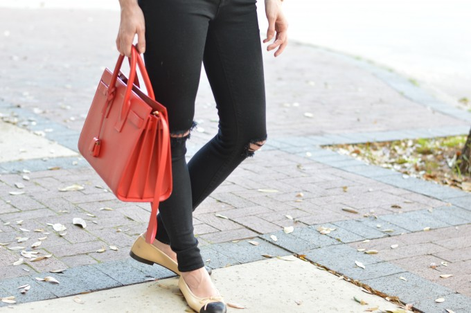 black distressed jeans, red statement bag, chanel flats