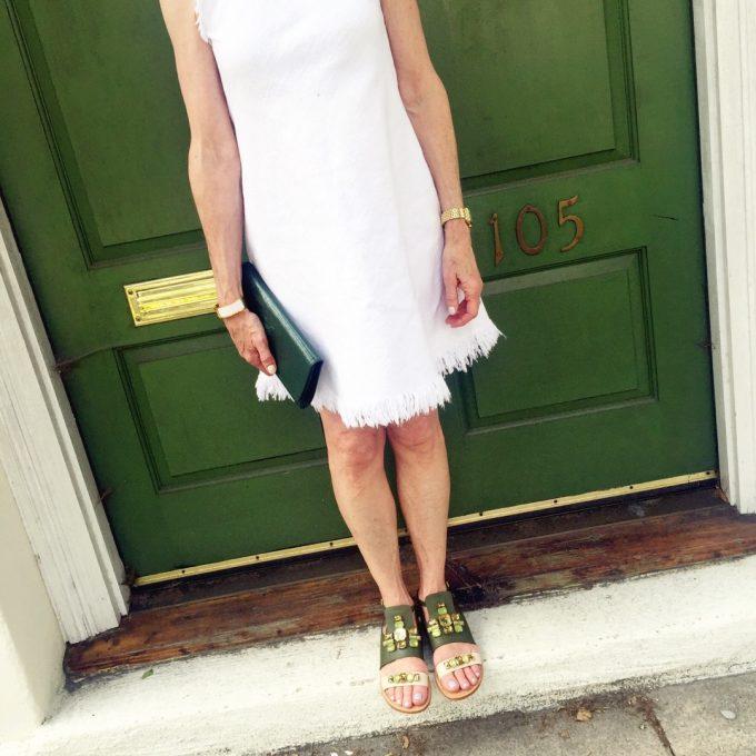white dress with frayed hem, embellished green sandals, green clutch