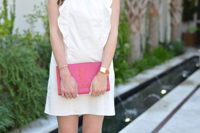 hot pink clutch, gold watch with orange strap