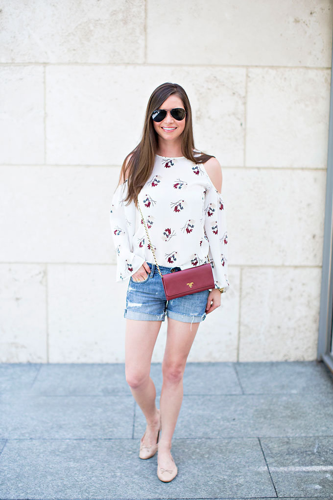 A fall transition style with a floral cold shoulder top, distressed boyfriend shorts, Prada wallet on a chain and classic ballet flats