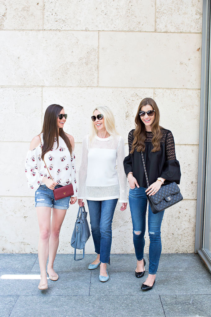 A mom, daughter and daughter-in-law wearing a cold shoulder top, winter white sweater and black poplin boho style top, carrying Prada wallet on a chain, baby blue suede satchel and a classic Chanel bag.