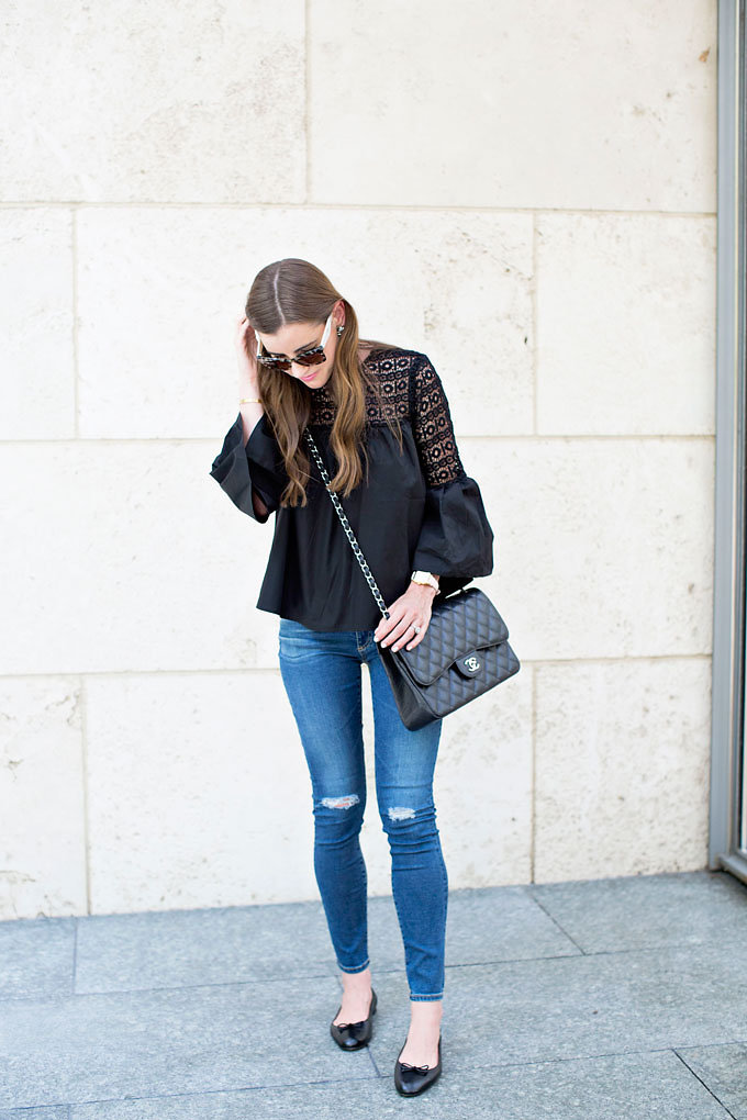 A boho chic black top with lightly distressed jeans, a Chanel double flap bag and black ballet flats