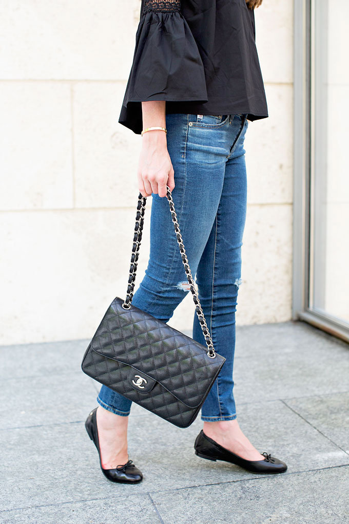 Lightly distressed jeans with a classic Chanel handbag and black ballet flats