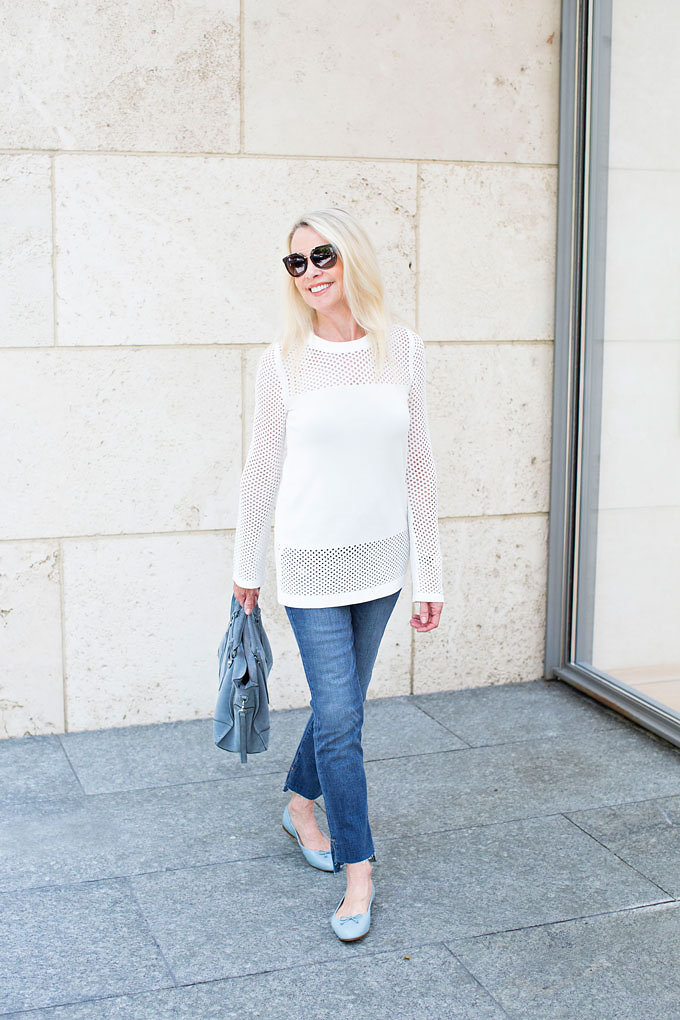 A winter white sweater with sheer sleeves and neckand hemline with jeans and a blue suede handbag and baby blue ballet flats