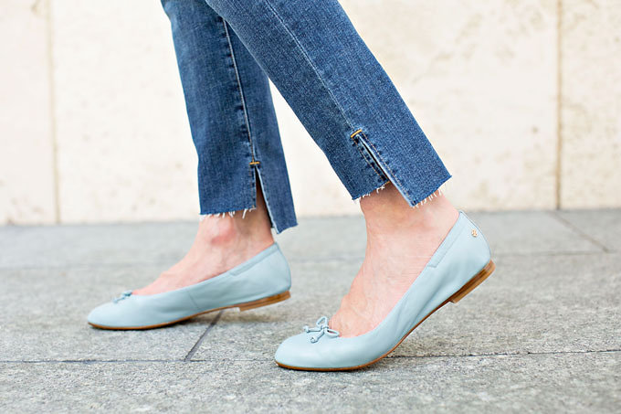 A pair of baby blue ballet flats with an unusual notched ankle jean