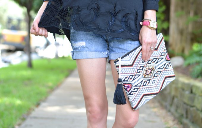 cut out hem on black top, distressed boyfriend shorts, tribal clutch, silver and gold watch with hot pink strap