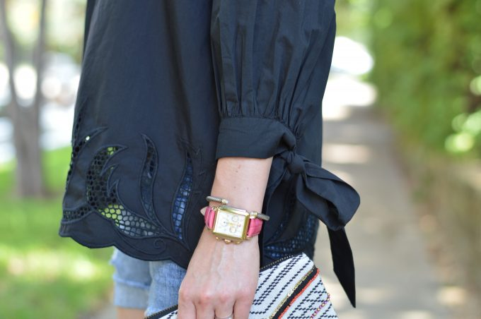 black top with tie sleeves, ladies silver and gold watch with hot pink strap, tribal clutch
