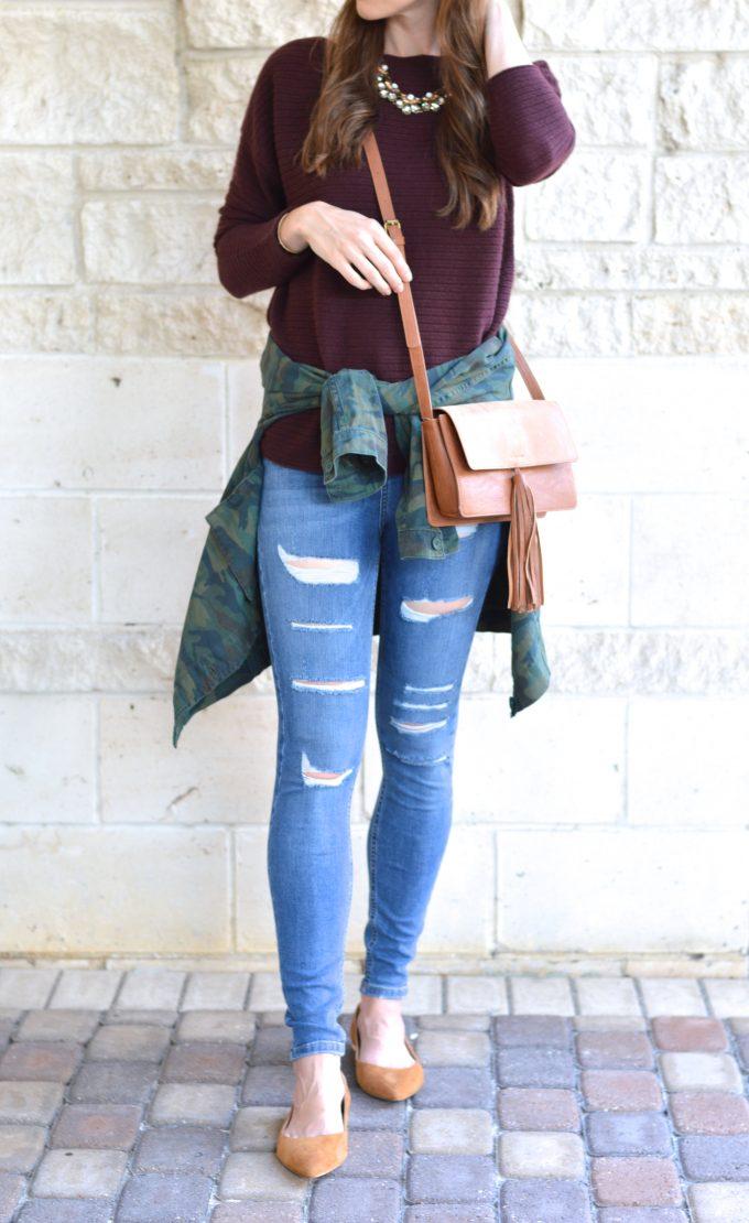 distressed jeans. camo jacket, oxblood sweater