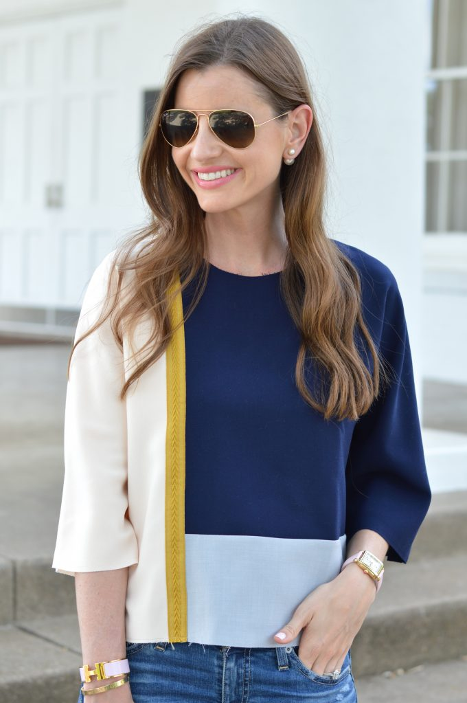 A fall transition look showing a unique colorblock top in navy, gray and blush pink with a gold brocade going down one side.