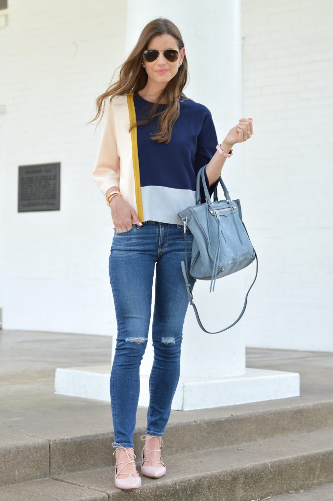 A fall transition look showing a unique colorblock top in navy, gray and blush pink with a gold brocade going down one side, distressed jeans and gray-blue suede tote bag