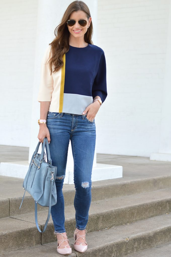 A fall transition look showing a unique colorblock top in navy, gray and blush pink with a gold brocade going down one side, distressed jeans and blush pink lace up flats.