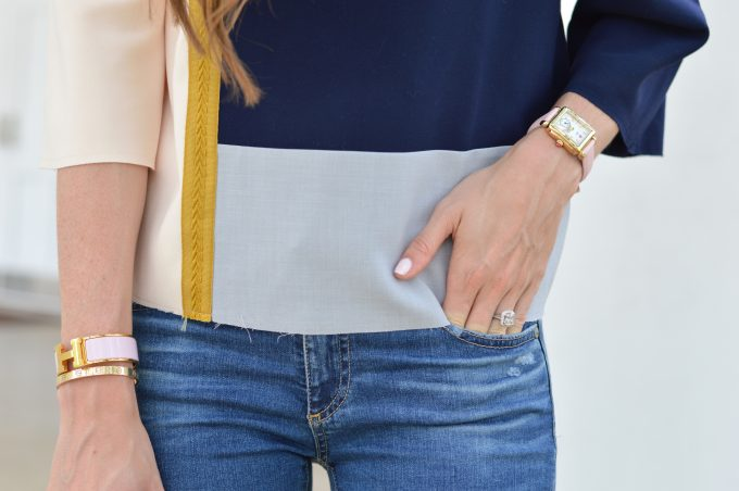A close up shot of a colorblock top in navy, gray and blush pink with a gold watch and strap in blush pink