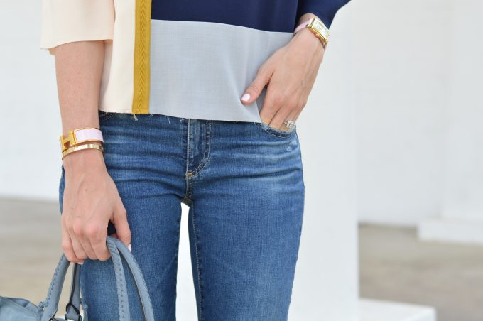 A close up shot of a colorblock top in gray, navy and blush pink