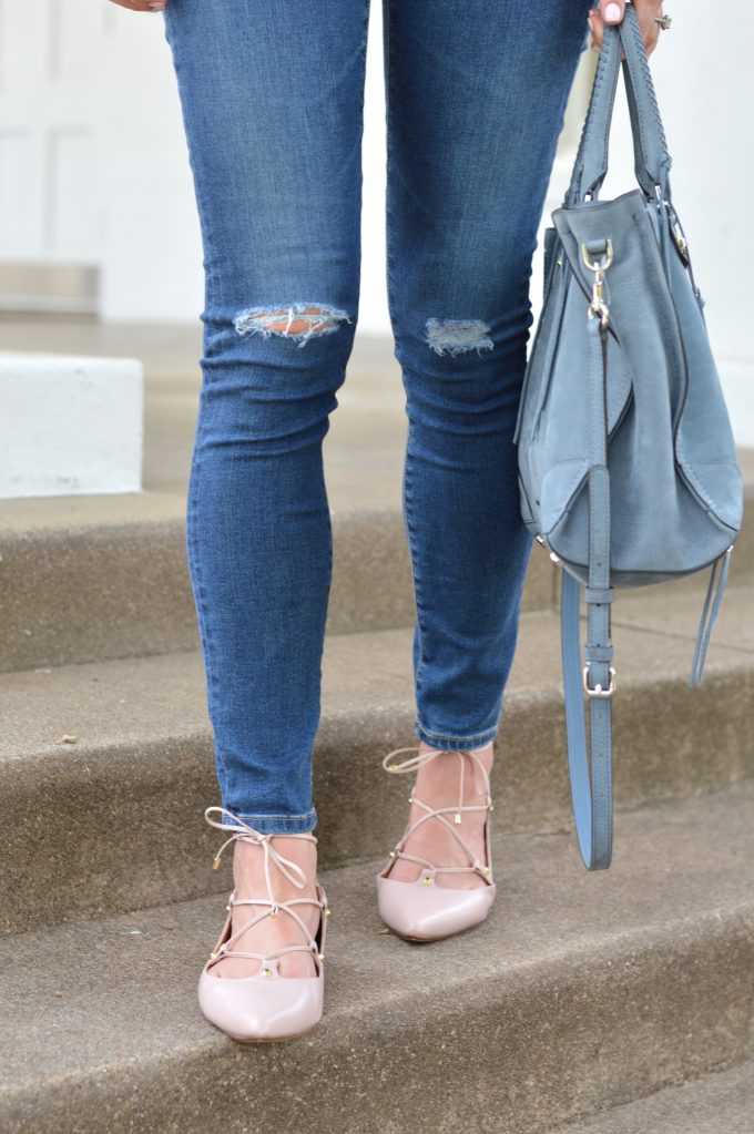 a detail shot showing distressed jeans, blush pink lace up flats and a gray-blue suede tote bag