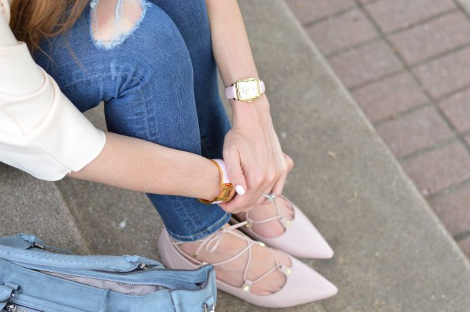 a close up detail of blush pink lace up flats and a gold watch face with blush pink strap