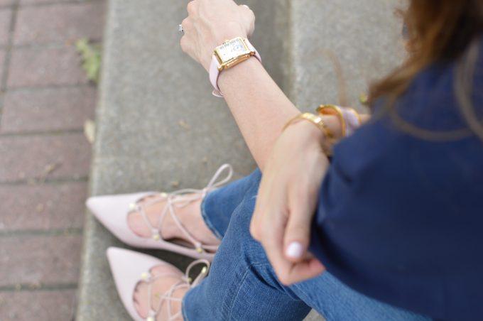 A beautful blush pink watch strap on a gold ladies watch with matching blush pink lace up flats.
