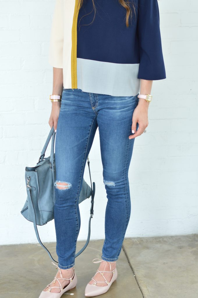 A great fall trasition look of a colorblock top in navy, gray and blush pink worn with distressed jeans, carrying a gray-blue suede tote bag and wearing blush pink lace up flats