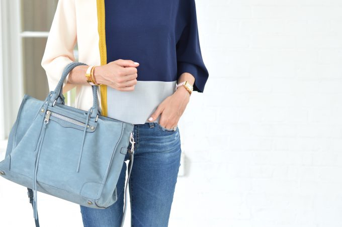 a colorblock top in navy, gray and blush with a suede tote bag in the same blue gray tones as the top