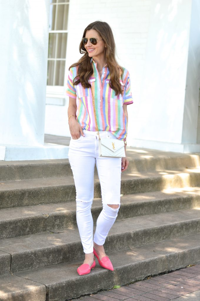 bishop and holland wearing white distressed jeans, a rainbow striped top and a white cross body bag