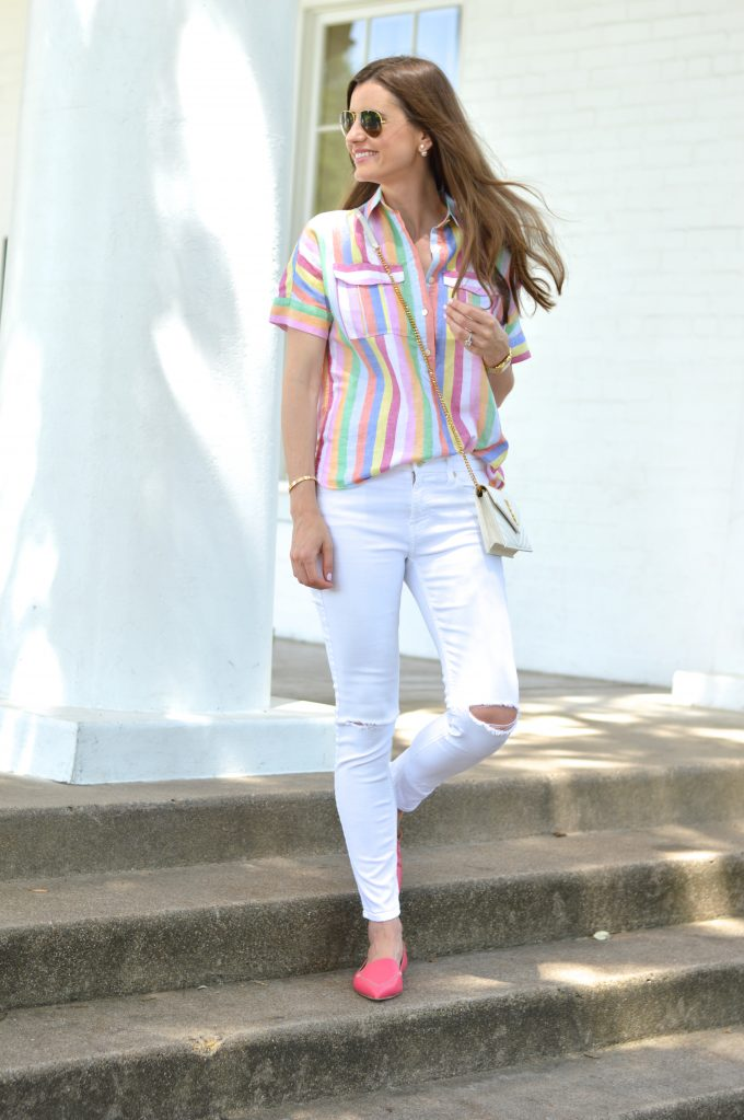 bishop and holland wearing white distressed jeans, a rainbow striped top and a white cross body bag with hot pink loafers