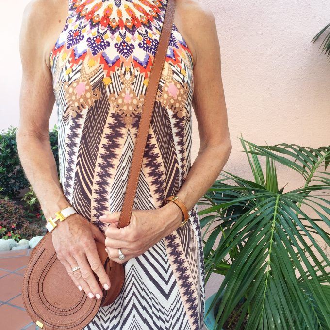 A tribal print dress with saddle colored crossbody bag