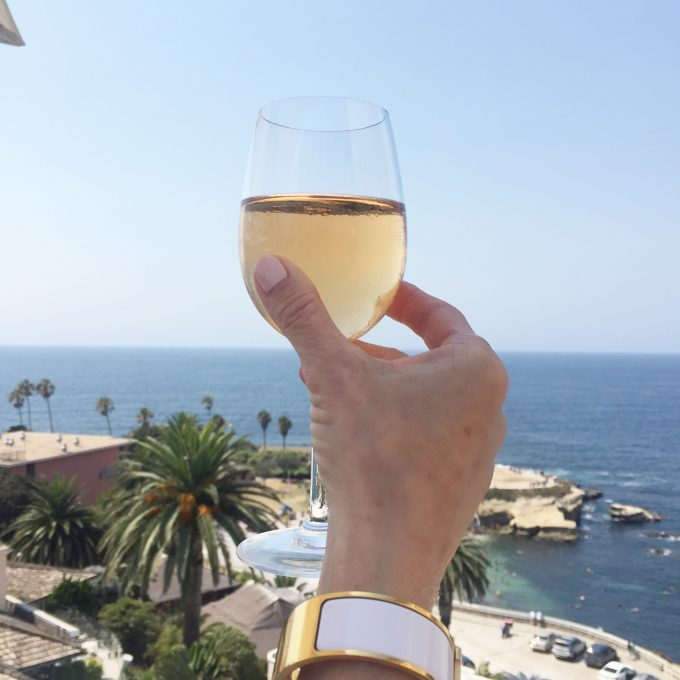 A glass of rose being raised up in front of a beautiful view of the Pacific Ocean at La Jolla California