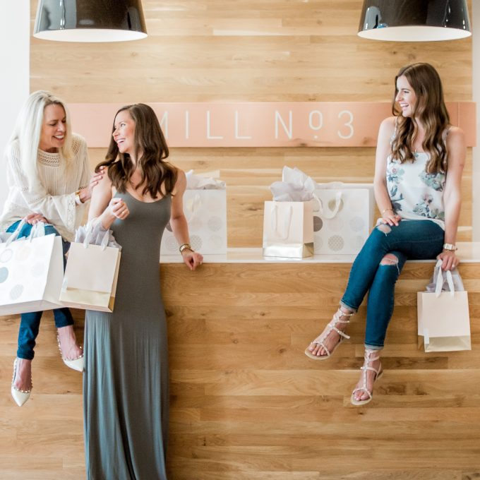 Three ladies laughing while sitting on a boutiques register desk after shopping thier sale.
