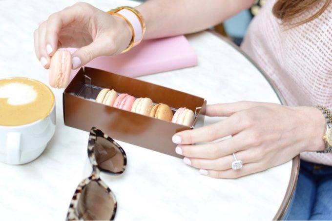 A woman sitting at a table with a box of French macarons, her pink weekely planner and her Prada tortoise shell sunglasses