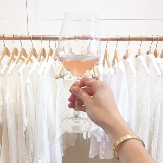 A glass of rosé being raised in front of a rack of clothing in shades of white