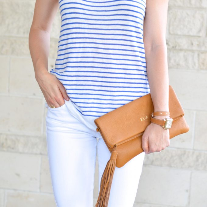 A blue and white striped tank top with white jeans and a saddle colored clutch
