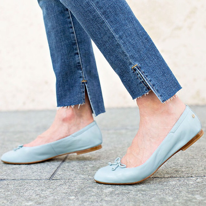 Jeans awith an uneven hem worn with baby blue ballet flats