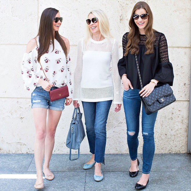Three ladies walking together laughing.