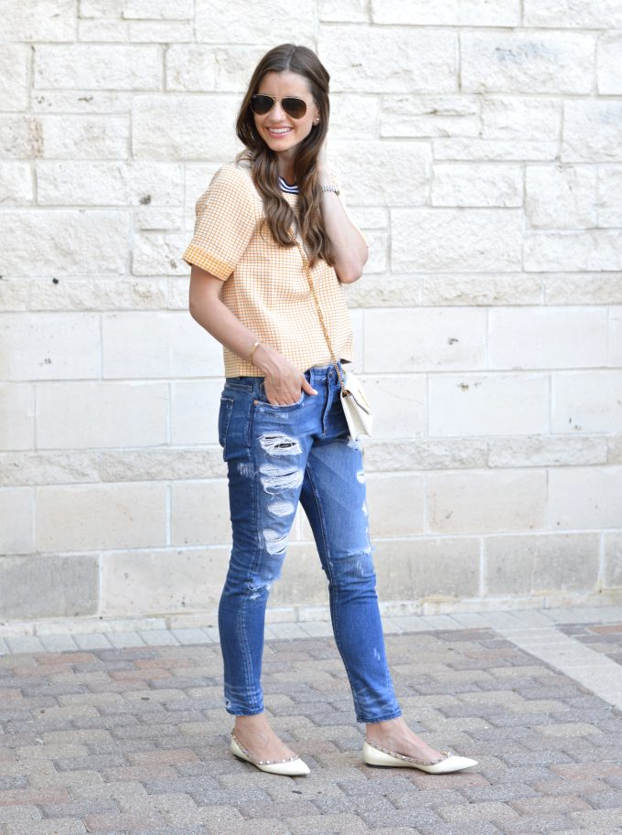 distressed boyfriend jeans worn with a boxy yellow top and a white cross body