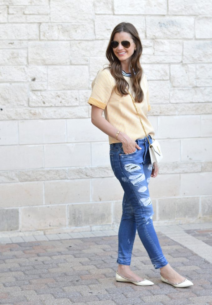 yellow boxy top and distressed boyfriend jeans and white cross body bag