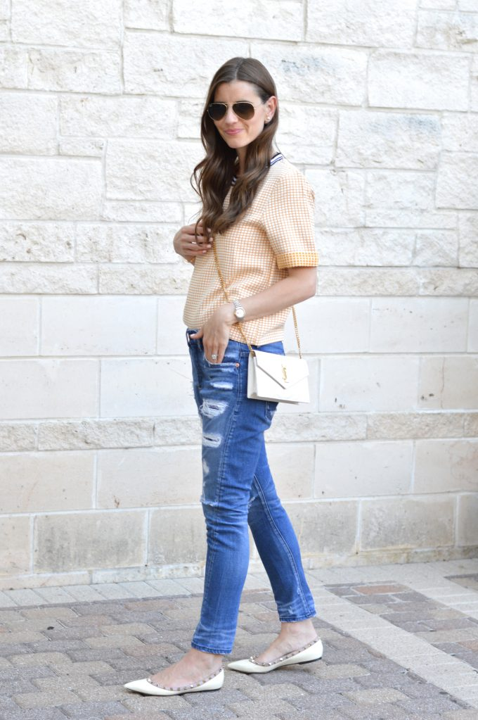 yellow boxy top with distressed boyfriend jeans and white cross body bag