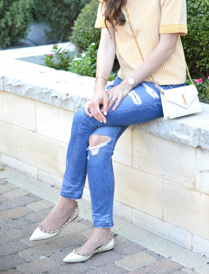 distressed boyfriend jeans and white cross body bag