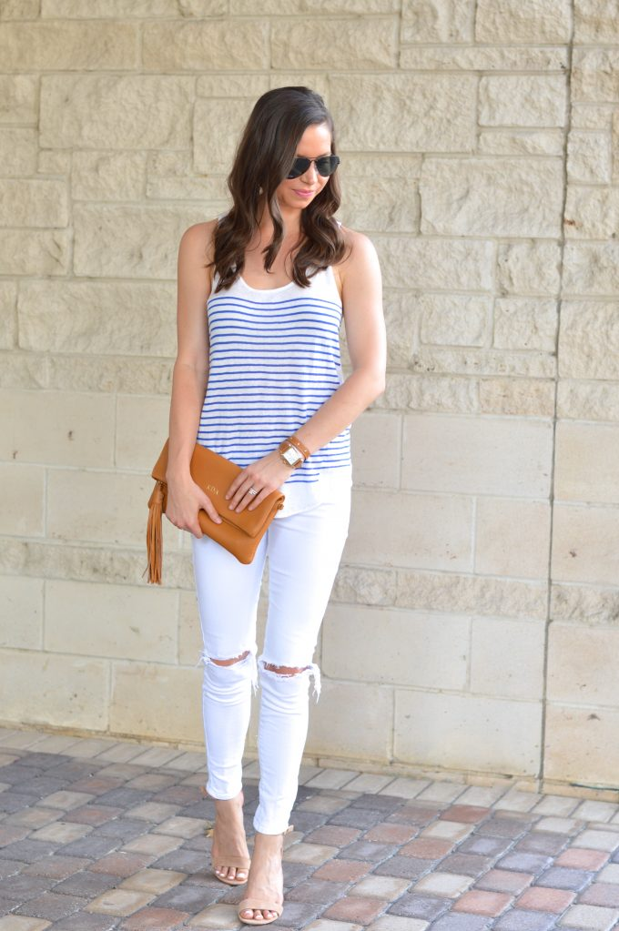 A casual date night look with a striped blua dn white tank, white distressed jeans, a monogrammed clutch in brown and nude heels.