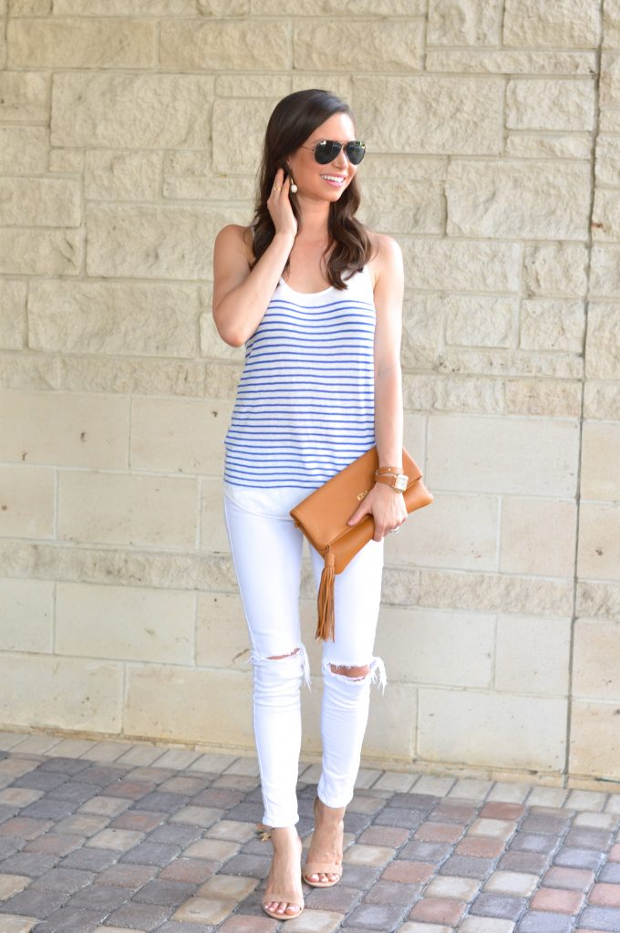 A casual date night look wearing a blue and white striped tank with white distressed jeans, carrying a monogrammed clutch with tassel in saddle brown.