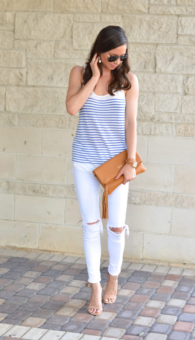 A blue and white stripe tank with white distressed jeans and a saddle brown monogrammed clutch.