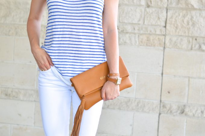 A mnogrammed clutch in luggage brown with a tassel and a ladies watch with a matching wrapstrap and a blue and white striped tank.