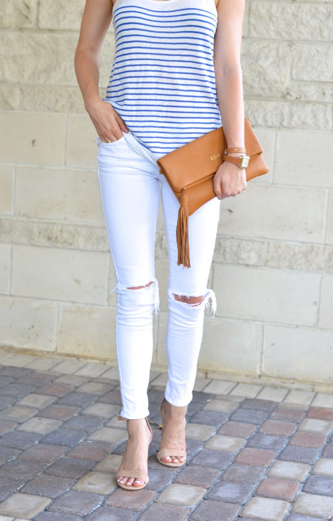 A blue and white striped tank with white distressed jeans, a brown monogrammed clutch with tassel and and a ladies watch with a brown wrap strap.