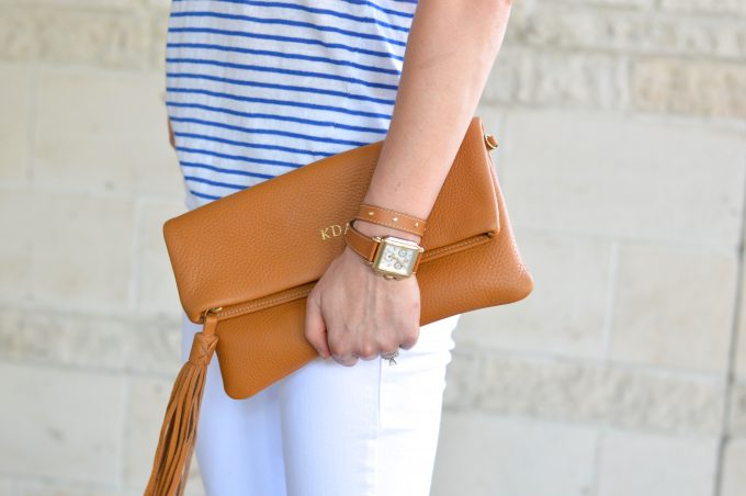 A monogrammed clutch in brown with a wrap watch strap in brown.