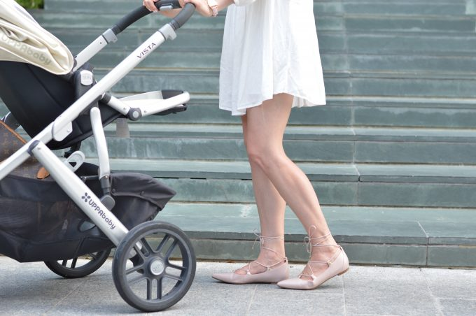 Young stylish mother pushing her baby in a stroller in a darling white dress and blush pink lace up flats