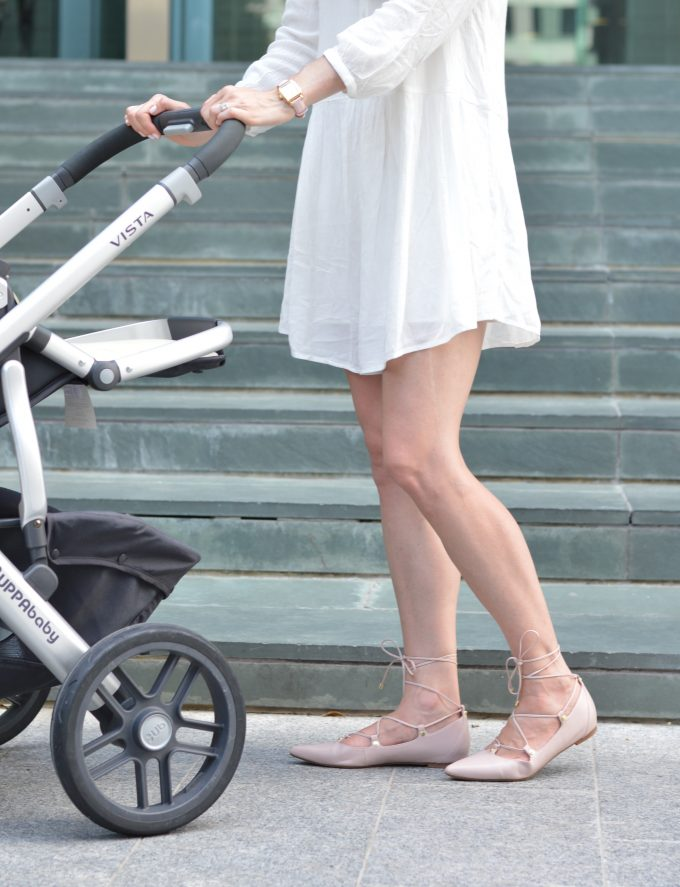 Young mother pushing baby in his stroller wearing a cute white dress and blush pink lace up flats