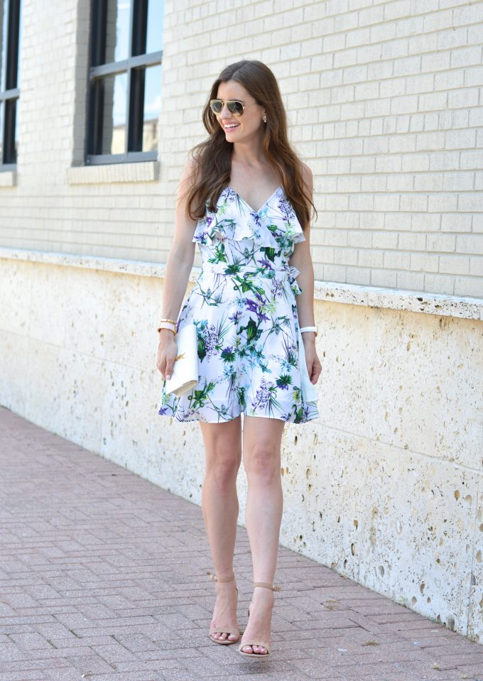 A feminine wrap dress with ruffle neckline worn with a white clutch and nude heels.
