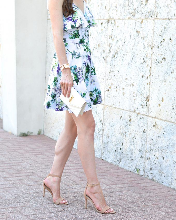 A feminine floral wrap dress with a white clutcha and neutral heeled sandals.