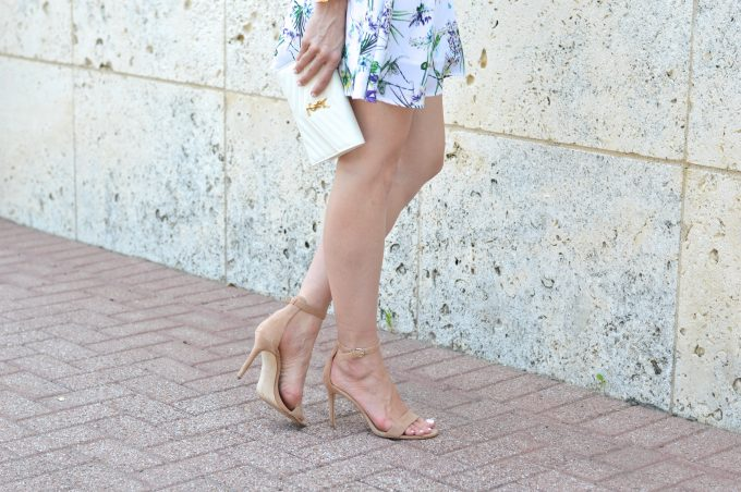 Nude sandals worn with a feminine floral dress and a white clutch.